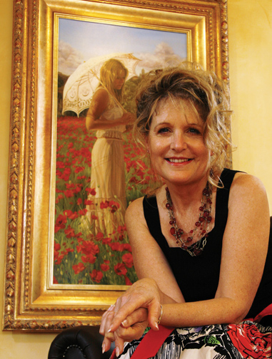 Susan Harrison-Tustain in her studio next to her painting featuring girl with umbrella in red poppy field in Provence, France. Susan is an internationally acclaimed artist, author, workshop art teacher, how to paint DVD and how to paint video download demonstrator. Susan Harrison-Tustain writes free painting lessons in her blog for artists of all painting skill levels.